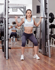 Athletic woman doing squats at the gym