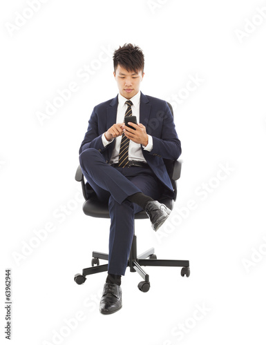 asian businessman touching smart phone on chair