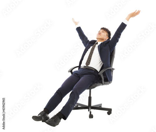 relax businessman sitting on a chair and raise hands