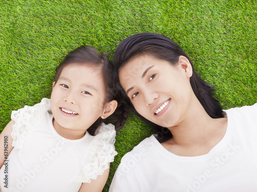 smiling mother and daughter lying on a meadow