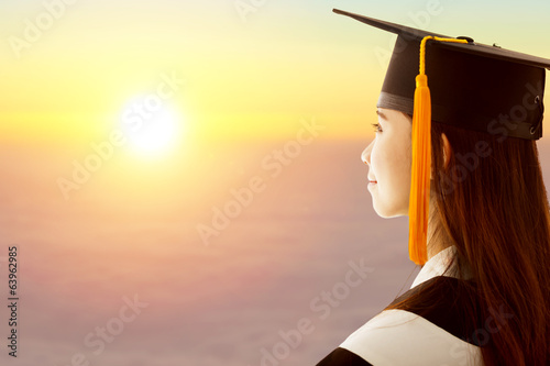 female graduation is thinking future with sunset background