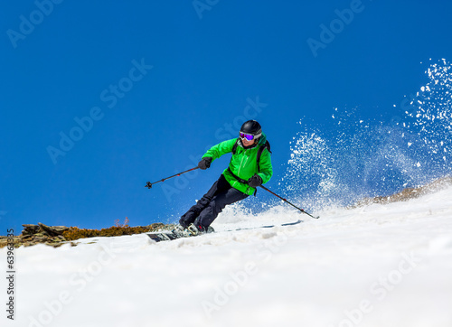 Woman skier on a sky background
