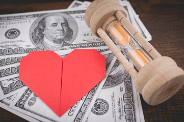 Heart, sandglass & banknotes: concept for love, money & time