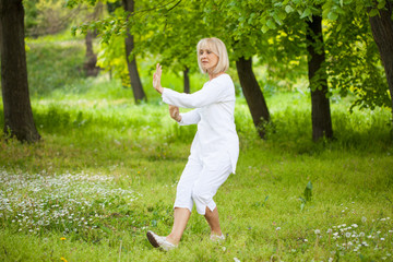 senior woman in white practising tai chi
