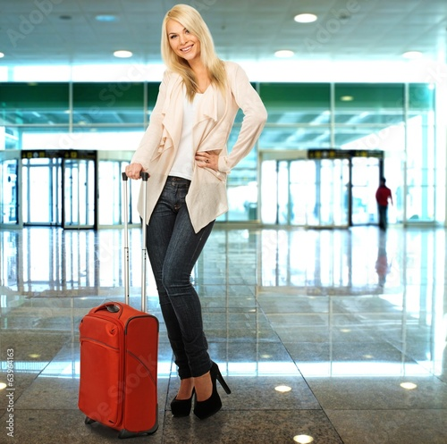 Blond woman with suitcase in airport