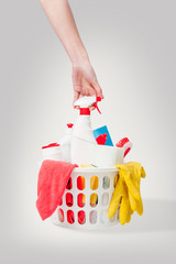 Woman hand picking up cleaning products from basket