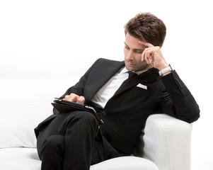 Uomo elegante su divano con tablet