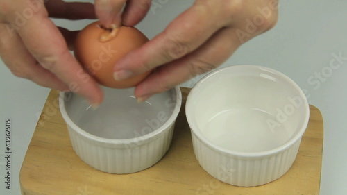 Separating the yolk from the white of an egg.