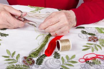 Seniorin beim Sticken einer Tischdecke