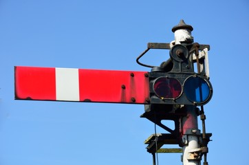 Red rail signal with blue sky