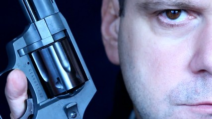Closeup portrait of a man with a gun looking forward