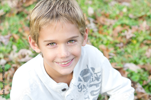 Tween Boy sitting outside in the grass.
