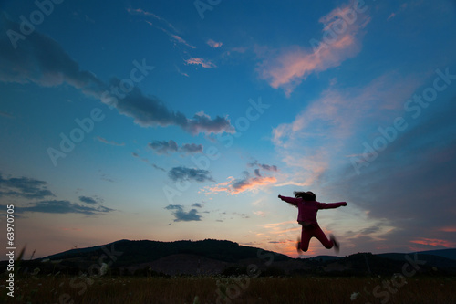 silhouette of happy kid jumping on sunset