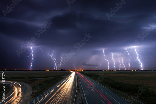 Storm Thunderstorm and lightnings in night over a highway with car lig