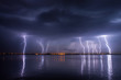 Leinwanddruck Bild - Thunderstorm and lightnings in night over a lake with reflaction