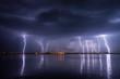 Leinwandbild Motiv Thunderstorm and lightnings in night over a lake with reflaction
