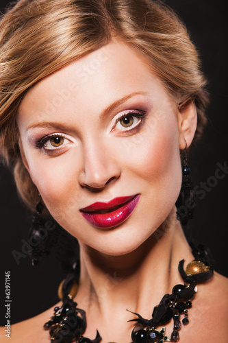 beautiful model with make-up, red lips and wearing black jewelry