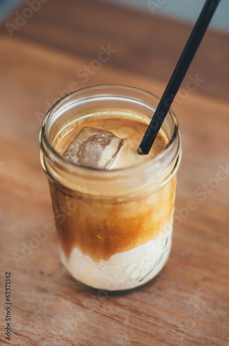 Close up cold coffee drink with ice on wood table