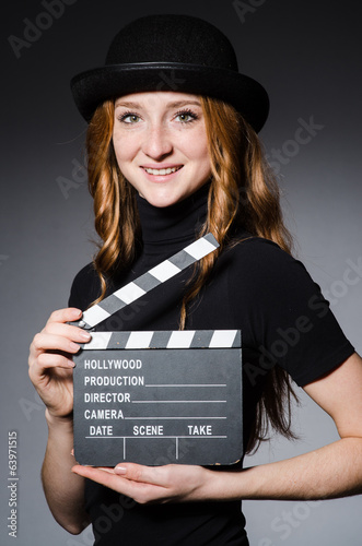 Young redhead girl in hat with movie board against grey backgrou