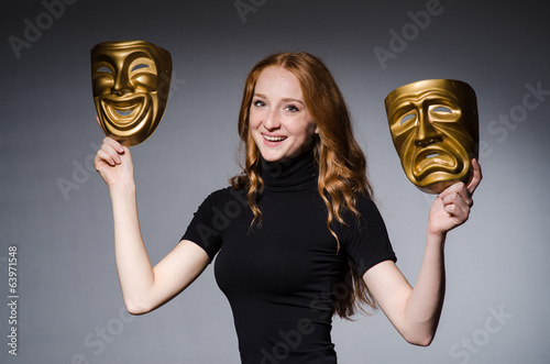 Redhead woman iwith masks in hypocrisy consept against grey back