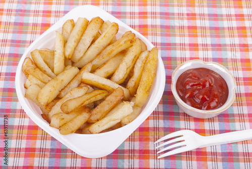 Fried potatoes in a plate on a tablecloth.