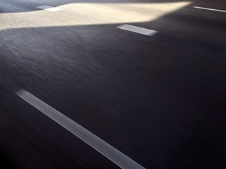 Fast lane on the highway with lane marking on gray tarmac.
