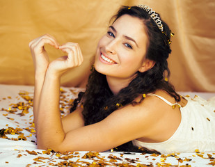 Beauty young princess with gold confetti and tiara, smiling