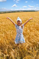 happy small girl dancing in a field