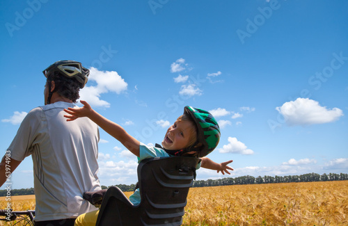 little girl  and father riding bike on the field