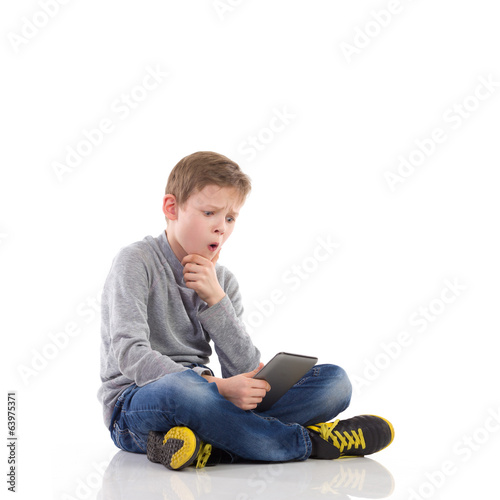 Surprised boy using a tablet.