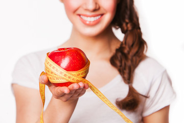 smiling woman holding an apple and tape measure