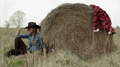 Beautiful blonde girl relaxing close to sheaf of hay