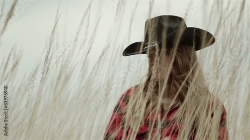 Portrait of a cowboy girl standing in the field of grain