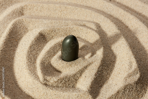 Black stone sticking out of the sand