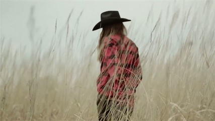 Girl in cowboy hat walking across the field of grain