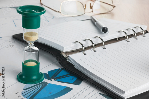 Hourglass, diary, glasses and pen