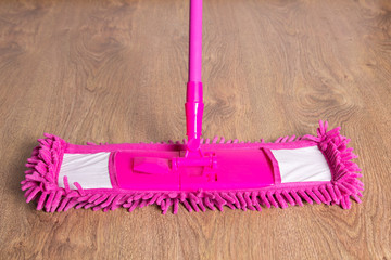 close up of pink cleaning mop on wooden floor