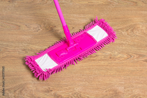 cleaning wooden floor with pink mop