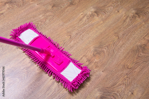 cleaning the parquet floor with pink mop