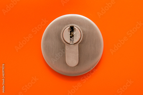 close up of keyhole on orange door