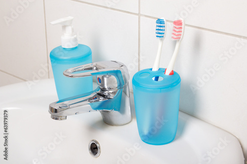 tooth brushes and soap on white sink