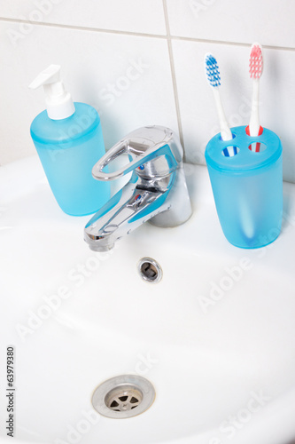 close up of tooth brushes and soap on sink