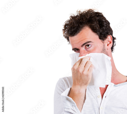 Sick man, blowing his nose, has cold, allergy