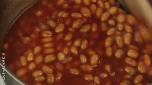A pot of baked beans being stirred with a spoon.