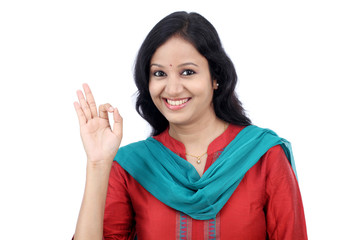 Cheerful young woman showing OK sign against a white background