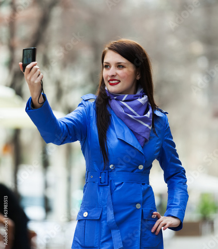 Female tourist with smartphone photographing