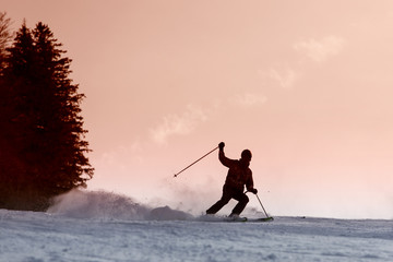Skier silhouette on a slope at sunset
