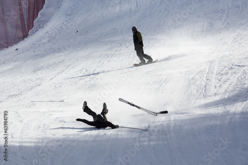 skier falling down white on mountain slope