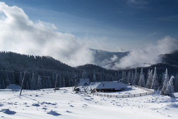 Caban in winter mountain with blue sky and white clouds
