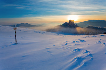 Metal signboard in snow on mountain in sunset